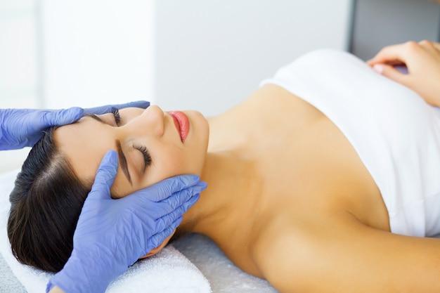 Pele e cuidados. mulher jovem e bonita com pele pura e bonita no salão spa. massagem para o rosto. deitado na mesa de massagem. massagem manual. alta resolução