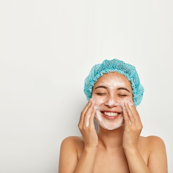 Pele impecável e com pureza. imagem vertical de mulher bonita lava rosto, goza água gelada, tem espuma na pele, sorri de alegria, fica de olhos fechados, cuida da higiene pessoal. conceito de bem-estar