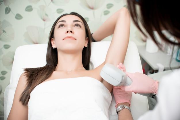 Pele lisa sob os braços. mulher na depilação a laser, cuidados com o corpo.
