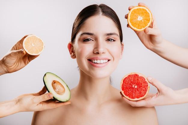 Pele radiante linda e saudável de mulher sem maquiagem. retrato de menina sorrindo contra a parede de frutas.