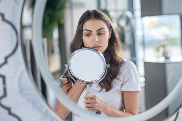 Pele saudável. uma mulher verificando sua pele enquanto se olha no espelho