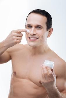 Pele suave. homem feliz e simpático positivo sorrindo e segurando uma garrafa de creme facial enquanto coloca a garrafa de creme na bochecha