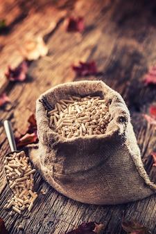 Pellets de madeira prensados de biomassa em saco velho.