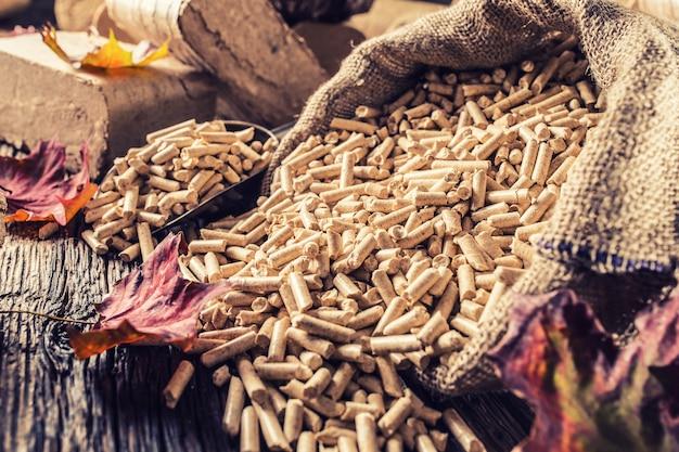 Pellets e briquetes de madeira prensados de biomassa com folhas de outono.
