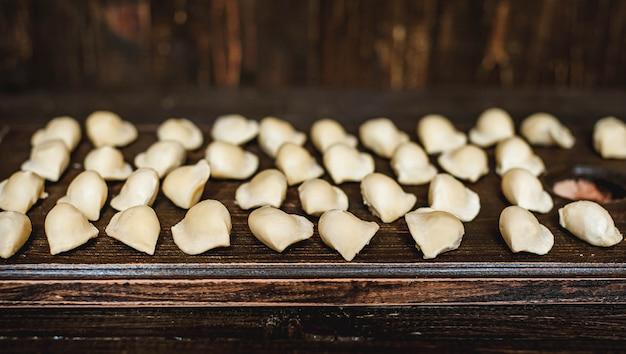Pelmeni, bolinhos de massa com carne no fundo escuro de madeira. massa fresca.
