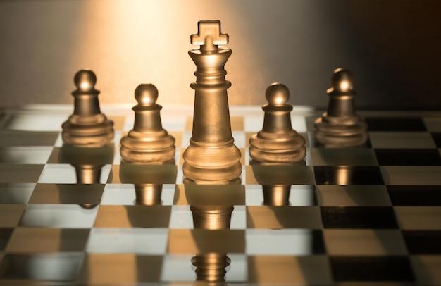 Pelotão de 5 peças de xadrez liderada pelo rei com fundo claro do sol.