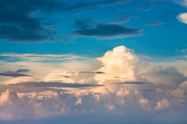 Peludas nuvens multicoloridas encaracoladas em um céu azul durante o pôr do sol