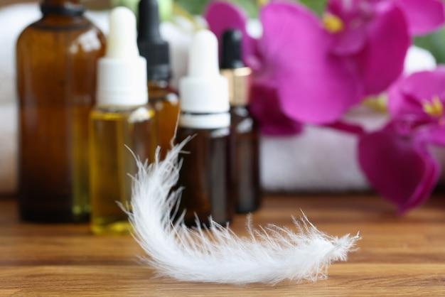 Pena branca deitada na mesa perto de cosméticos closeup