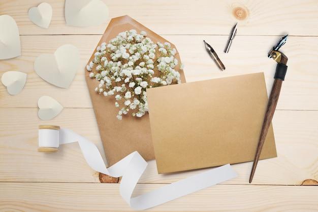 Pena caligráfica, um envelope com flores e uma carta, um cartão de felicitações para o dia dos namorados com lugar para o seu texto