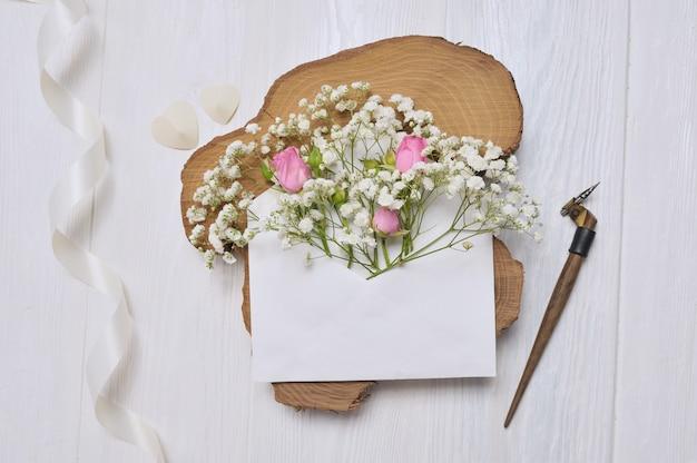 Pena caligráfica um envelope com flores rosa e uma carta, cartão de caixa de presente para dia dos namorados