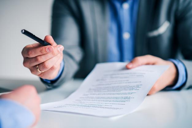 Pena de oferecimento do homem de negócios a outro homem de negócios para assinar o contrato ou o original.
