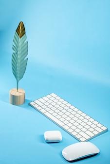 Pena de pássaro, teclado, mouse e fones de ouvido