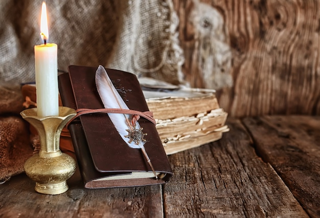Pena e livro romance perto de uma vela