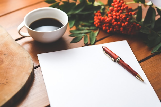 Pena em um pedaço de papel com um copo do fundo do café