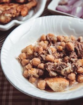Pena em um prato branco com cordeiro, cordeiro gordo, castanhas e ervilhas