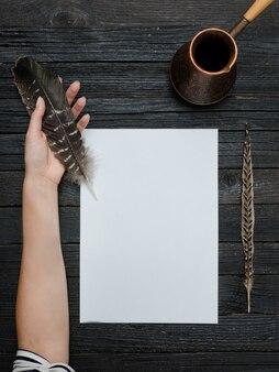 Pena em uma mão feminina, folha de papel limpa e cezve. mesa de madeira velha vista do topo