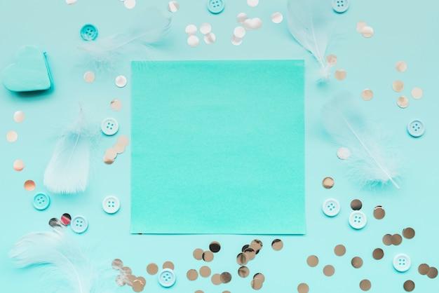 Pena; lantejoulas; botões cercados em torno do papel turquesa no pano de fundo azul-petróleo