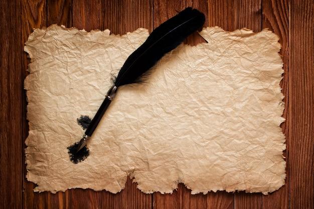 Pena preta e papel velho no fundo de uma mesa marrom