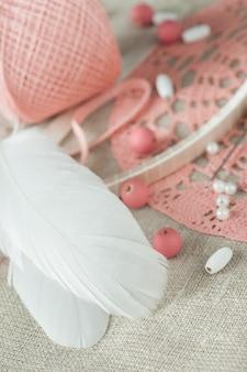 Penas brancas, pérolas, contas rosa