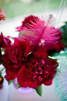 Penas cor-de-rosa e peônias vermelhas