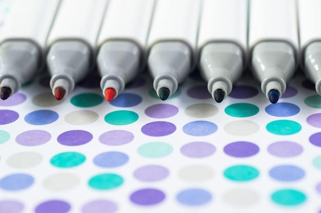 Penas de marcador de cores isoladas em papel de fundo