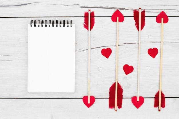 Penas decorativas em varinhas com pequenos corações perto de caderno
