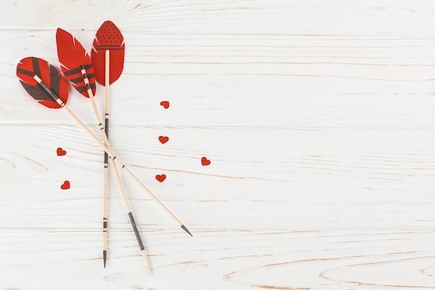 Penas decorativas em varinhas perto de pequenos corações