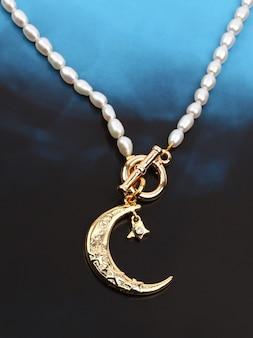 Pendente de lua crescente dourada com colar de pérolas em fundo gradiente preto azul
