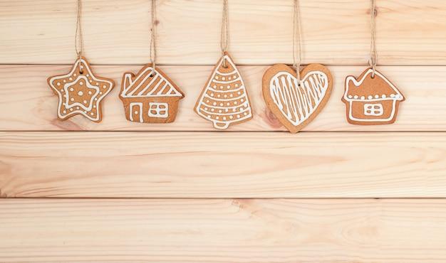 Pendurando biscoitos de natal em um fundo de madeira