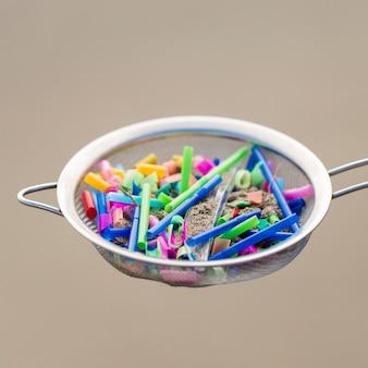Peneira com pedaços de plástico