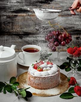 Peneira de açúcar em pó de mulher no bolo de frutas