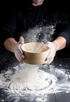 Peneira de madeira redonda com farinha nas mãos masculinas