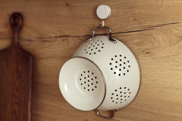 Peneira de metal branco pendurada no gancho na parede de madeira da cozinha.