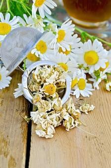 Peneira de metal com camomila seca, um buquê de flores frescas de camomila, chá em um copo de vidro em um fundo de tábuas de madeira