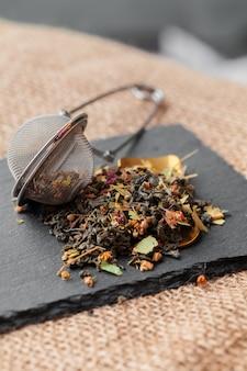 Peneira de metal com chá de ervas secas em um copo de vidro sobre a mesa