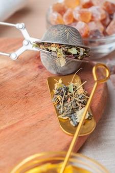 Peneira de metal com chá de ervas secas em um copo de vidro