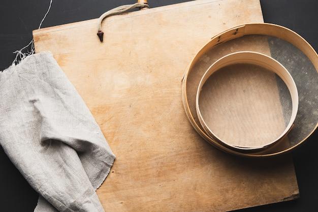 Peneira redonda de madeira vintage, guardanapo de linho cinza, mesa preta, vista de cima, utensílios de cozinha para fazer massa