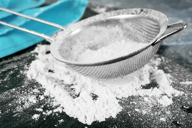 Peneirando a farinha pela peneira na mesa de madeira, closeup