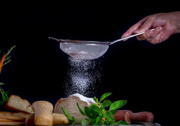 Peneirando farinha em um pão em uma mesa de madeira com uma variedade de pães