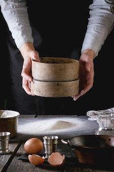 Peneirar a farinha pelas mãos femininas
