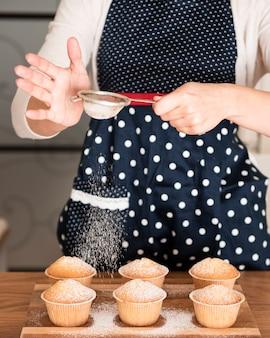 Peneirar açúcar em pó em muffins de mulher