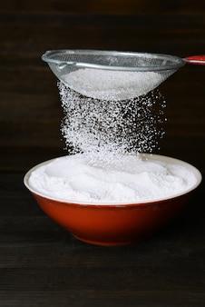 Peneirar farinha em uma tigela na mesa de madeira