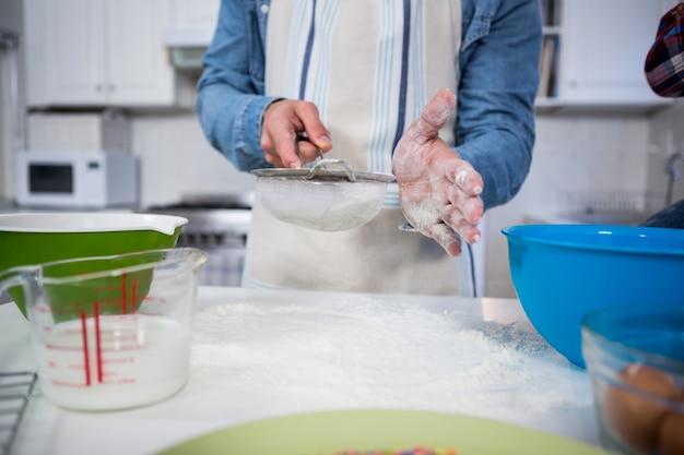 Peneirar farinha por uma peneira