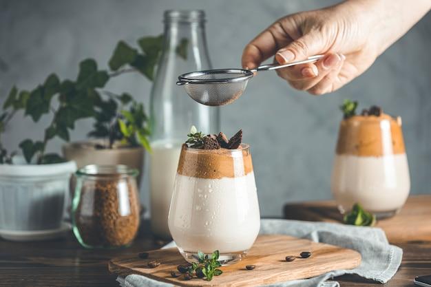 Peneirar o cacau em pó por peneira sobre um copo de bebida gelada com espuma dalgona coffee