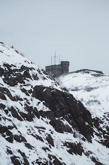 Penhasco e edifício coberto de neve durante o dia