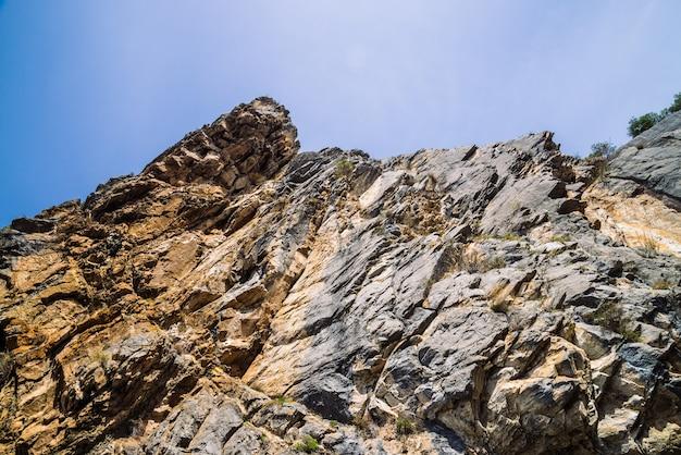 Penhasco grande da montanha sob o close-up do céu nebuloso.