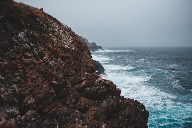 Penhasco perto das ondas do mar e nevoeiro