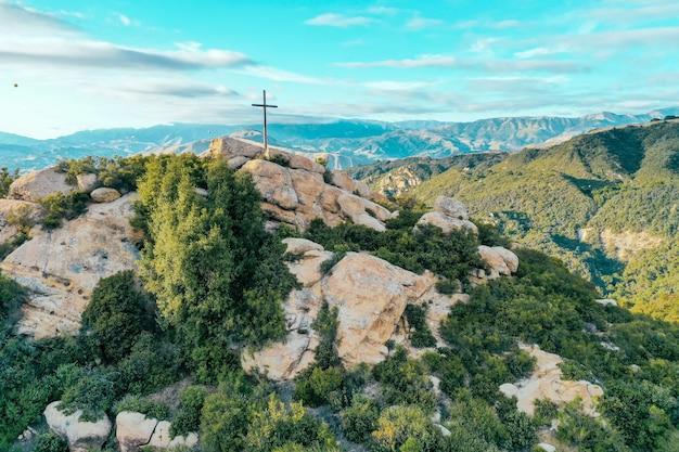 Penhasco rochoso coberto de vegetação com uma cruz colocada no topo e belas montanhas