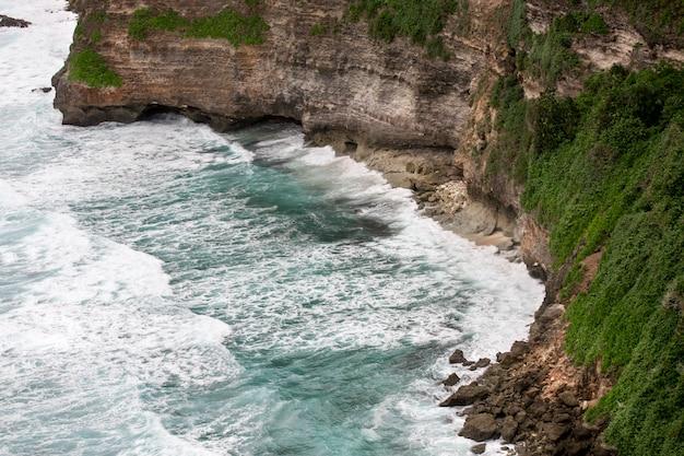 Penhascos acima do mar tropical azul com paisagem verde. nusa dua. uluwatu bali indonésia