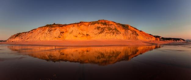 Penhascos da costa basca iluminados pelo sol ao anoitecer na praia de ilbarritz em biarritz, no país basco.